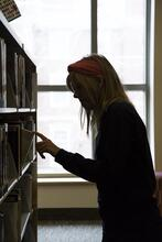 Photo of a woman picking a book off a shelf.
